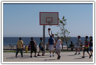 Guys playing basketball on the beach